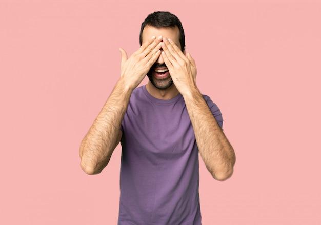Knappe mens die ogen behandelt door handen. verrast om te zien wat er op een geïsoleerde roze achtergrond staat te gebeuren