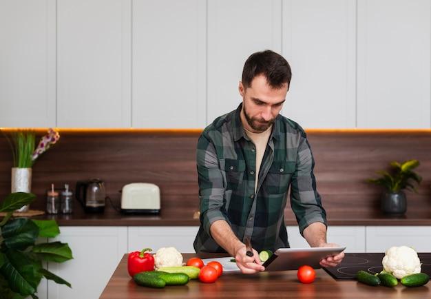 Knappe mens die op tablet in keuken kijkt