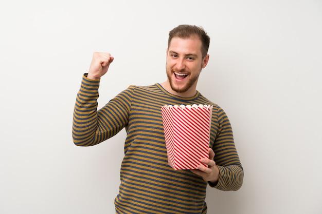 Knappe mens die over geïsoleerde witte muur een kom popcorns houdt