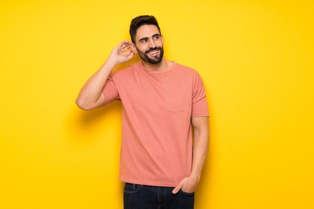 Knappe mens die over gele muur een idee denkt terwijl het krassen van hoofd
