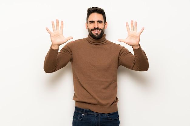 Knappe mens die over witte muur tien met vingers telt