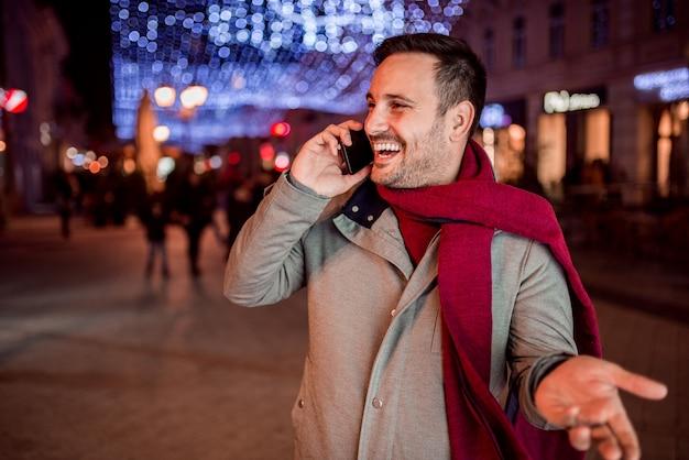Knappe mens die terwijl het spreken op mobiele telefoon bij nacht in verfraaide stadsstraat lachen.