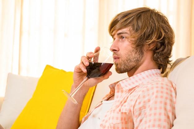 Knappe mens die van een glas wijn op de laag in de woonkamer geniet
