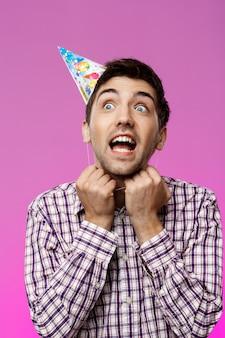 Knappe mens die verjaardagshoed over purpere muur proberen op te stijgen.