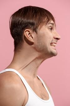 Knappe mens die verrast kijkt die op roze muur wordt geïsoleerd