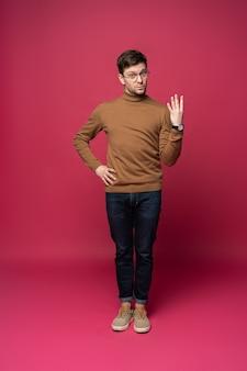 Knappe mens die vier met vingers over geïsoleerde blauwe achtergrond telt.