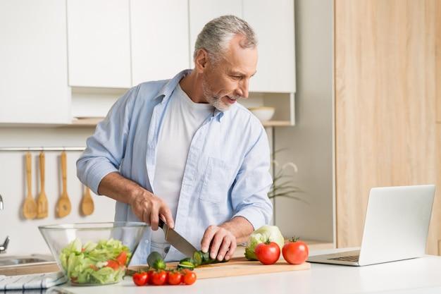 Knappe mens die zich bij de keuken bevindt die laptop en het koken gebruikt