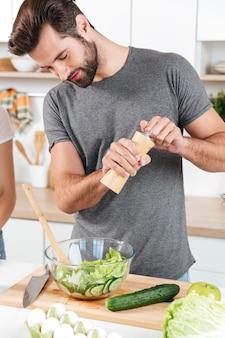 Knappe mens die zich bij keuken en het koken bevindt