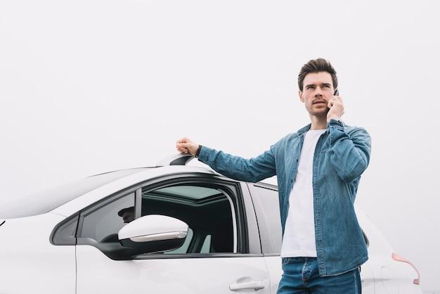 Knappe mens die zich dichtbij de auto bevindt die op cellphone spreekt