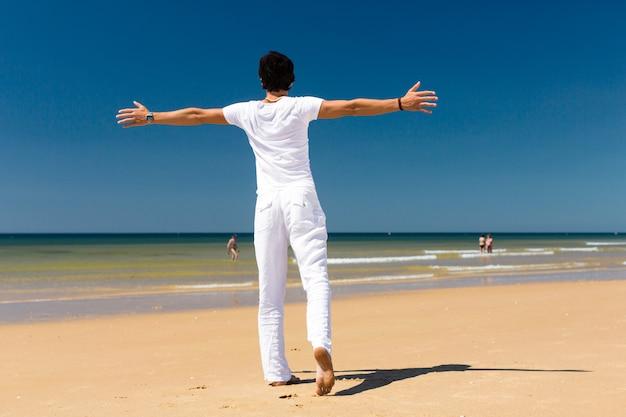Knappe mens die zich in de zon op strand bevindt