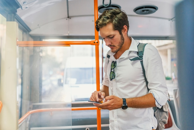 Knappe mens die zich in stadsbus bevindt en een bericht op de telefoon typt.
