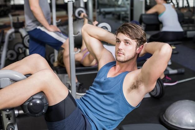 Knappe mens die zijn abs in gymnastiek werkt