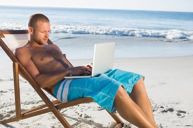 Knappe mens die zijn laptop met behulp van terwijl het ontspannen op zijn ligstoel