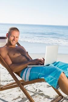 Knappe mens die zijn laptop met behulp van terwijl het zonnebaden