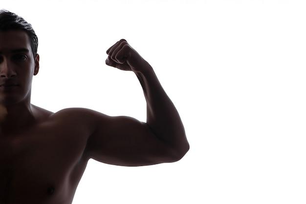 Knappe mens die zijn spieren op wit buigt