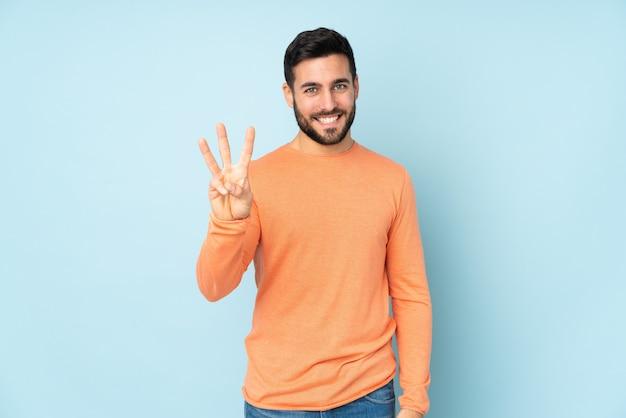 Knappe mens gelukkig en tellend drie met vingers over geïsoleerde blauwe muur