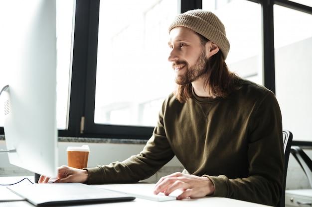 Knappe mens in bureau die computer met behulp van. opzij kijken.