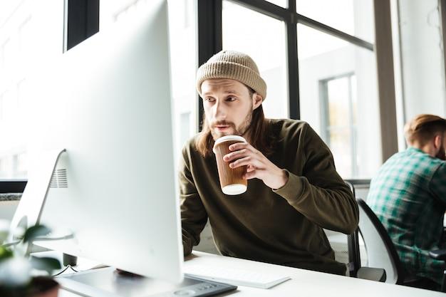Knappe mens in bureau die computer met behulp van