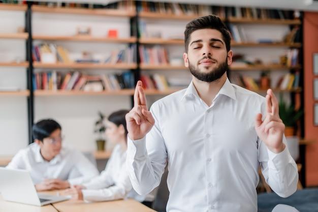 Knappe mens in de witte vingers van de overhemdsholding die in het bureau worden gekruist