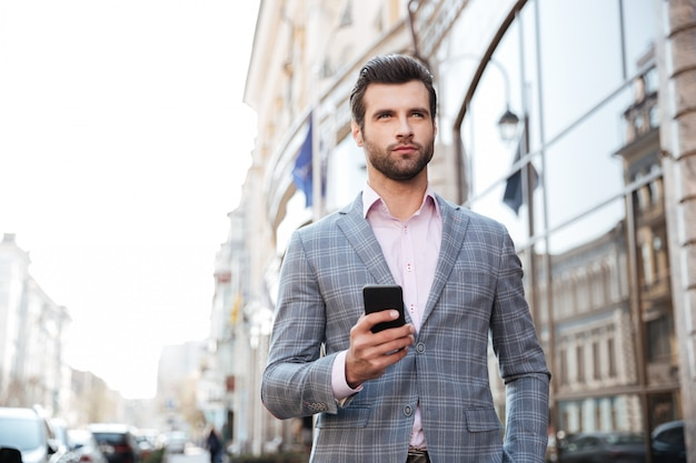 Knappe mens in een jasje die en mobiele telefoon lopen houden