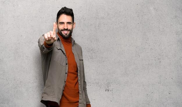 Knappe mens met baard die en een vinger over geweven muur tonen opheffen