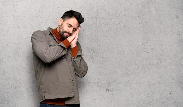 Knappe mens met baard die slaapgebaar in dische uitdrukking over geweven muur maken