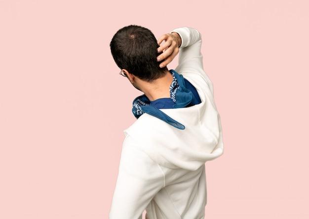 Knappe mens met glazen op achterpositie die terug terwijl krassend hoofd op geïsoleerde roze achtergrond kijken