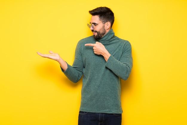 Knappe mens met zonnebril die copyspace denkbeeldig op de palm houden om een advertentie in te voegen