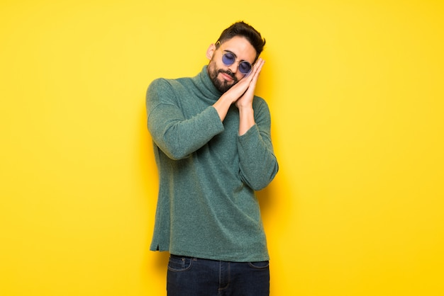 Knappe mens met zonnebril die slaapgebaar in dorable uitdrukking maken