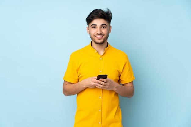 Knappe mens over geïsoleerde muur die een bericht met mobiel verzendt