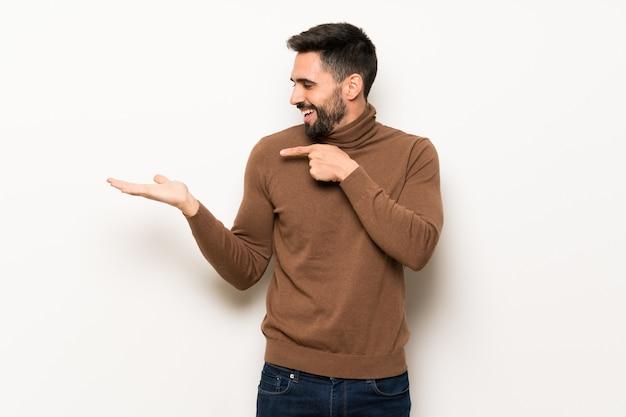 Knappe mens over witte muur die copyspace denkbeeldig op de palm houdt om een advertentie in te voegen