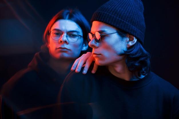Knappe mensen. portret van tweelingbroers. studio opname in donkere studio met neonlicht