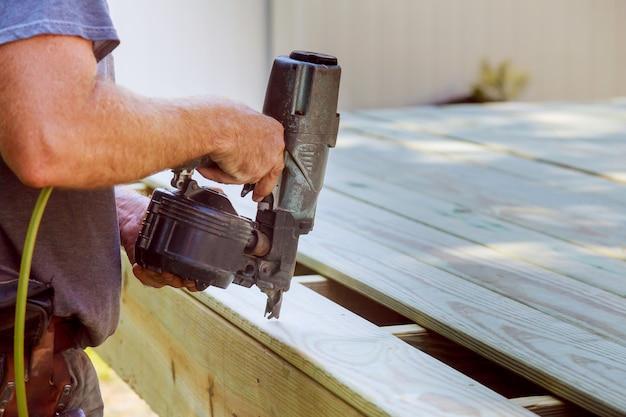 Knappe mensentimmerman die een houten vloer openluchtterras installeren in nieuw huis