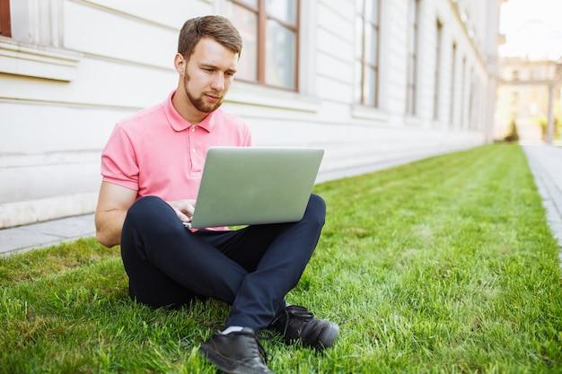 Knappe mensenzitting op het gras in de stad met laptop, baanonderzoek