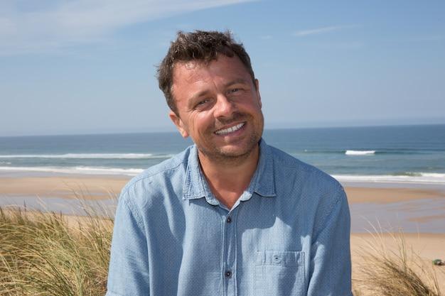 Knappe middelbare leeftijd man in casual kleding genieten van strand