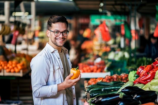 Knappe millenial man die verse groenten koopt bij straatmarkt.