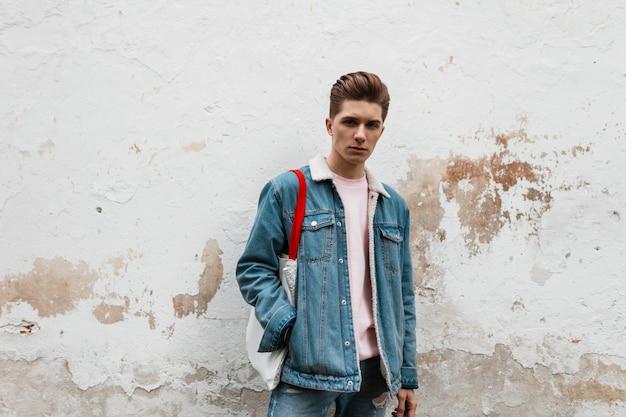 Knappe model knappe jongeman in stijlvol roze t-shirt in modieus blauw spijkerjasje met vintage stoffen shopper in de buurt van vintage muur in de stad. aardige vent in trendy slijtage buitenshuis. jeugd stijl.