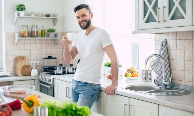 Knappe moderne lachende jonge bebaarde man drinkt wat koffie of thee uit zijn kopje en ontspannen in de keuken thuis
