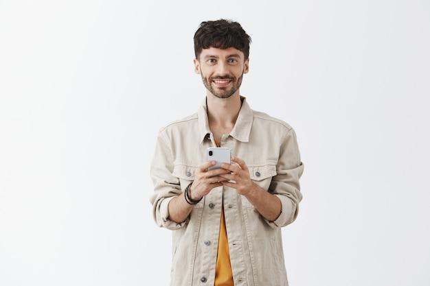 Knappe moderne man met behulp van mobiele telefoon en glimlachen