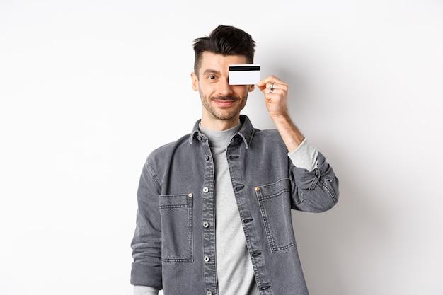 Knappe moderne man met snor, permanent in vrijetijdskleding en met plastic creditcard op oog, glimlachend tevreden op camera, witte achtergrond.