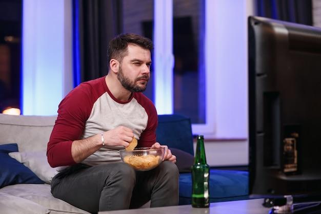 Knappe moderne, positieve 30-jarige man met goed verzorgde baard die van chipps geniet tijdens emotionele review van het spel van het favoriete voetbalteam op tv thuis