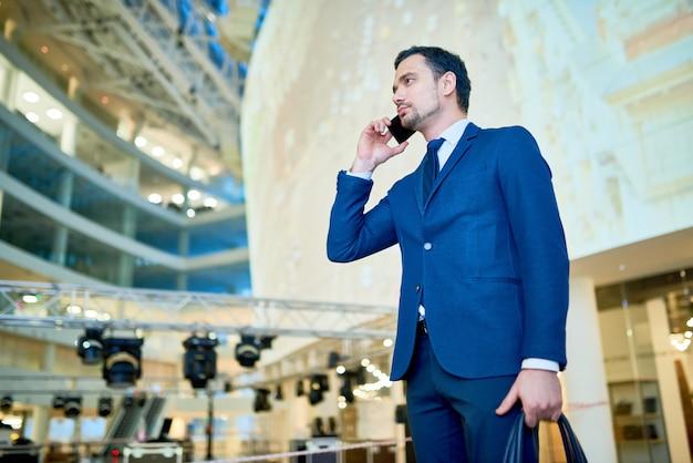 Knappe moderne zakenman spreken via de telefoon
