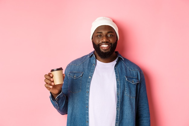 Knappe moderne zwarte man die afhaalkoffie drinkt, glimlacht en tevreden naar de camera kijkt, staande over roze achtergrond