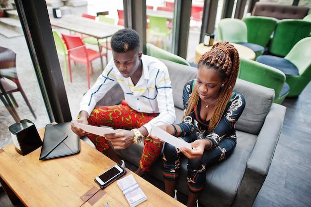Knappe modieuze afrikaanse amerikaanse paarzitting op kantoor en tekenbriefpapieren.