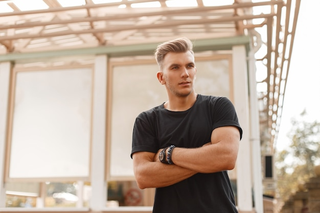Knappe modieuze amerikaanse man model met kapsel in zwart t-shirt op straat