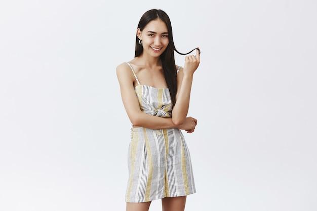 Knappe modieuze en vrouwelijke vrouw in zomeroutfit speelt met haarstreng, rolt het op de vinger en lacht sensueel, verleidt over grijze muur