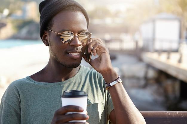 Knappe modieuze hipster met leuk telefoongesprek