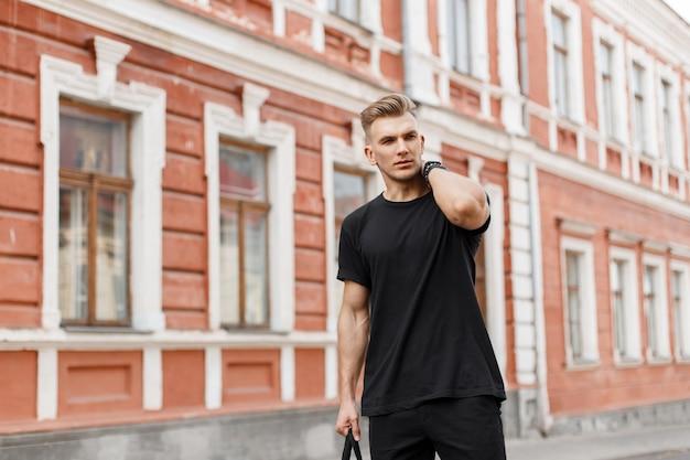Knappe modieuze jonge amerikaanse model man met kapsel in zwart t-shirt met zwarte tas lopen op straat in de stad