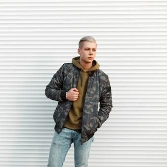 Knappe modieuze man in trendy militaire jas met hoodie poseren in de buurt van witte metalen muur