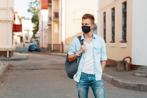 Knappe modieuze man met een medisch masker met een modieus spijkerhemd en een rugzak reist in de stad. epidemie en bescherming